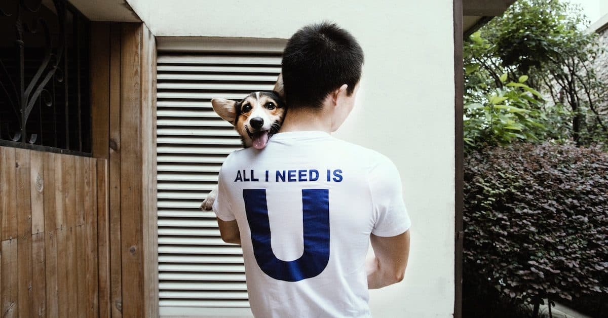 man with back of shirt that says all I need is U