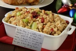 Dressing with cranberries in it, with notecard describing a Thanksgiving tradition for a fun Friendsgiving project.