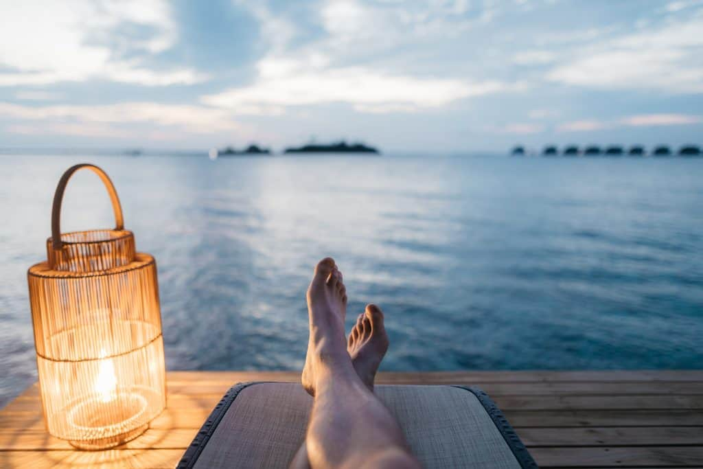 Person sitting on a dock looking out over the water. A self-care gift package.