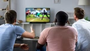 Three men watching football on Friensdgiving