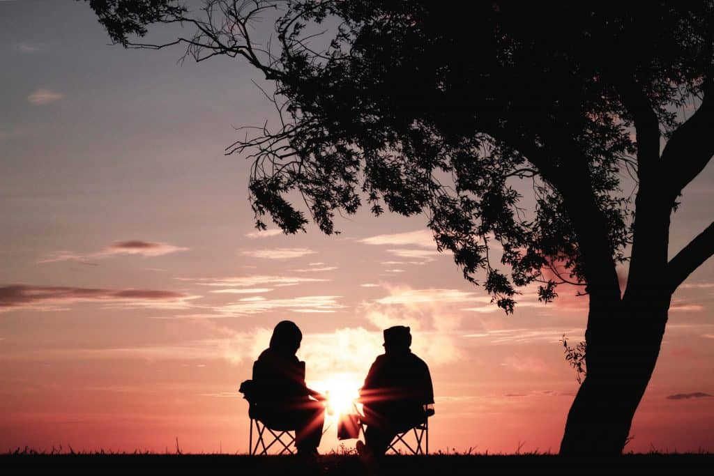 couple in camp chairs silhouetted by sunset