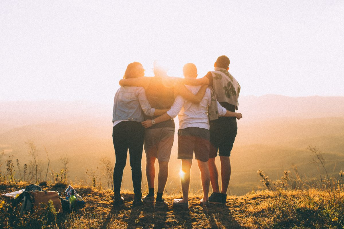 group of four friends standing in front of sunset