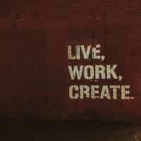 the words Live, Work, Create. on a dark red textured background