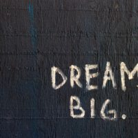 dream big written in chalk on dark, textured background