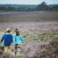 two children walking through field