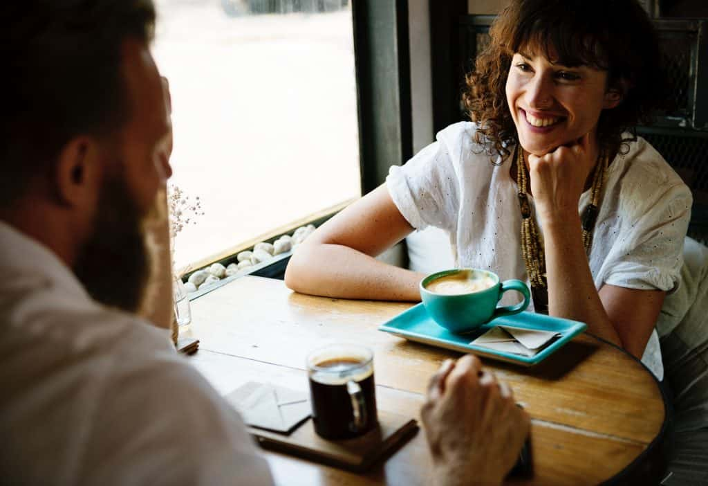 a man and a women conversing over coffee