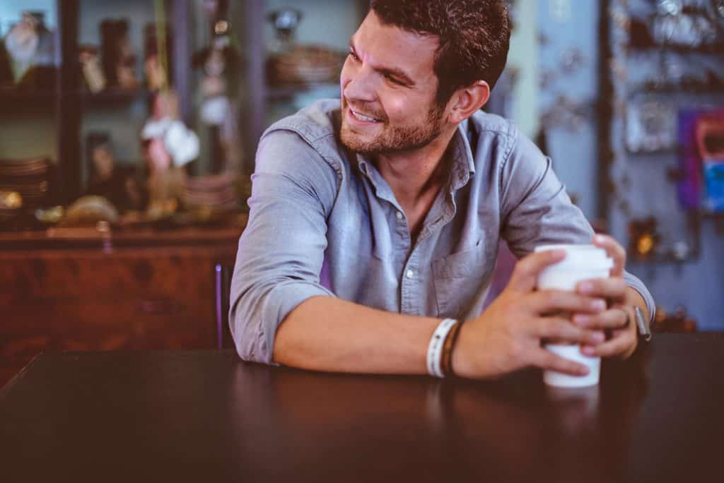 young man smiling in coffee shop