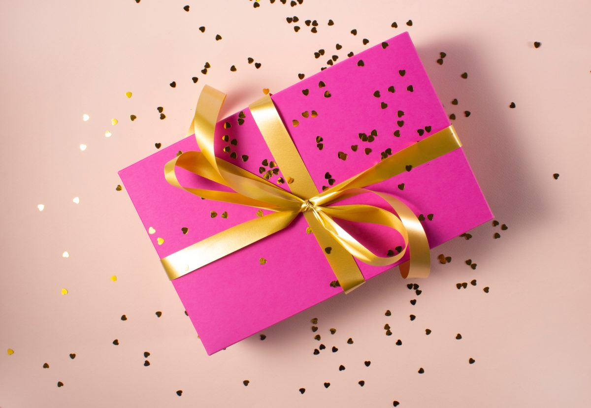 bright pink present with gold ribbon and confetti