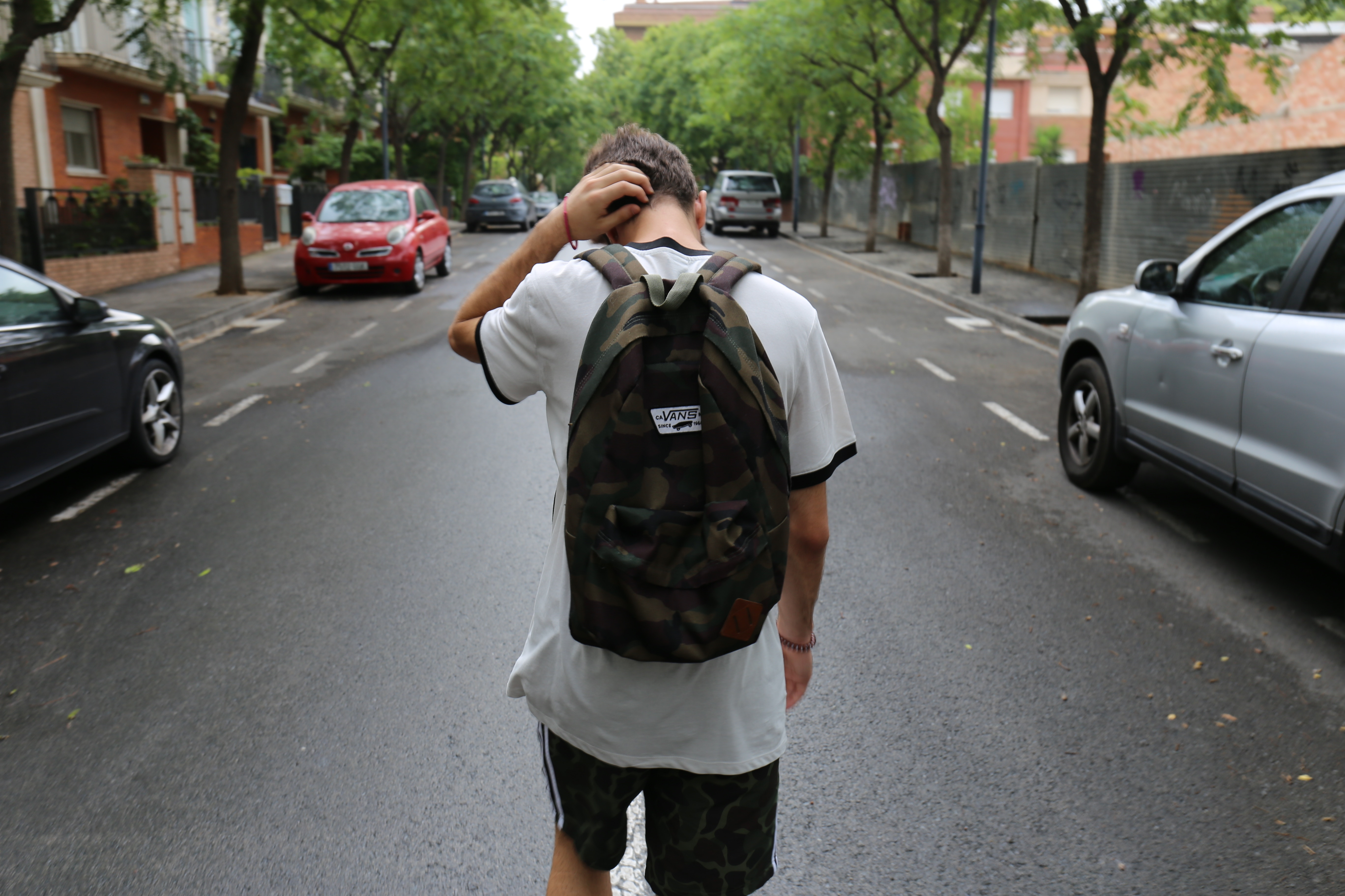 teenager with backpack walking away from viewer scratching his neck depressively