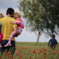 dad carrying one kid in each arm in a field