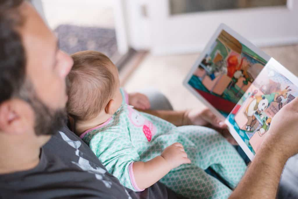 dad reading a picture book to his baby