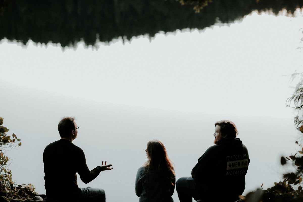 group of three friends discussing in front of a lake