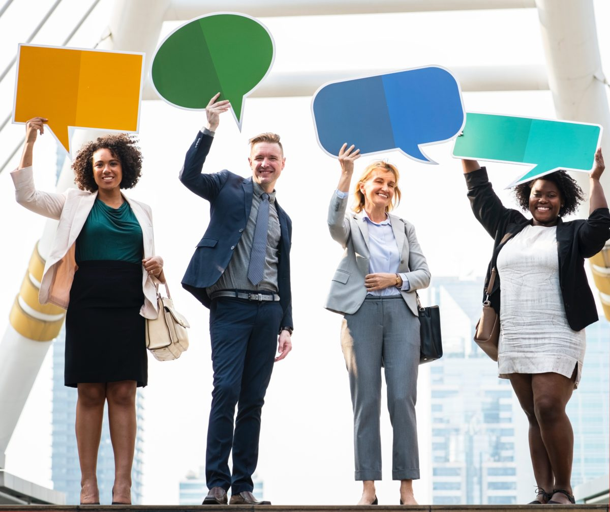 four people holding up comic speech bubbles